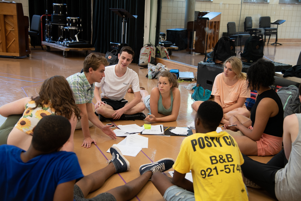 Beth Siegling (Sally Bowles, center) and her members of the 'Cabaret' ensemble dig into their scripts during rehearsal. Photo by Sarah Rolleri.