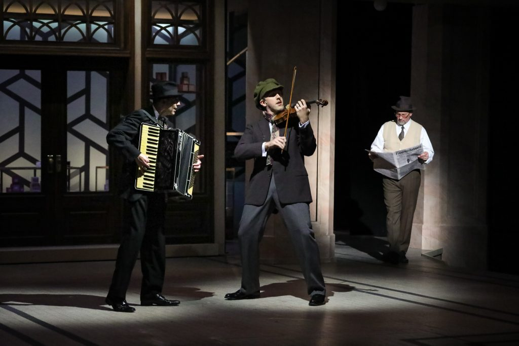 As part of the new orchestration, Mark Hartman and Dan Toot play the accordion and violin, respectively, in the prologue, as Jeffrey Blair Cornell's Sipos reads the newspaper in PlayMakers Repertory Company's production of SHE LOVES ME. (HuthPhoto)