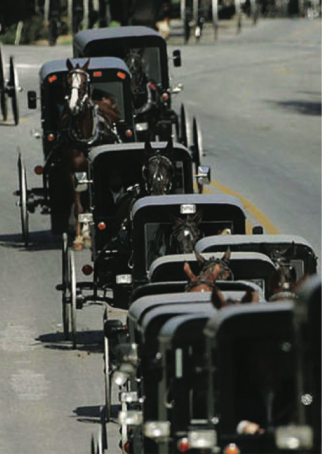 A funeral procession of horse and buggies during the funeral of victim Naomi Rose Ebersole on October 5th, 2006 Credit: Getty Images/Chris Hondros. Image courtesy of CBS News. title=
