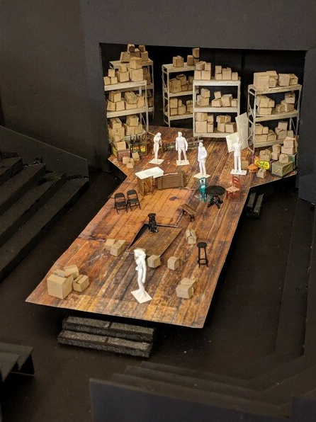 1/4-inch scale model of Jan Chambers' set design. A warehouse with a floor of aged wood, the impression of large windows, and shelves upon shelves of boxes all the way upstage.